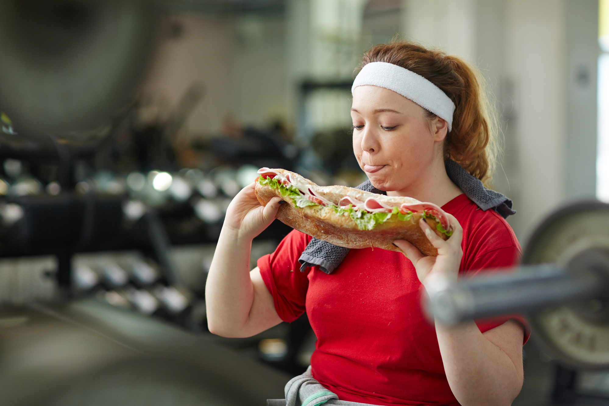 Portrait of young overweight woman licking her lips about to eat big fattening sandwich taking a break from work out in gym, concept of food obsession