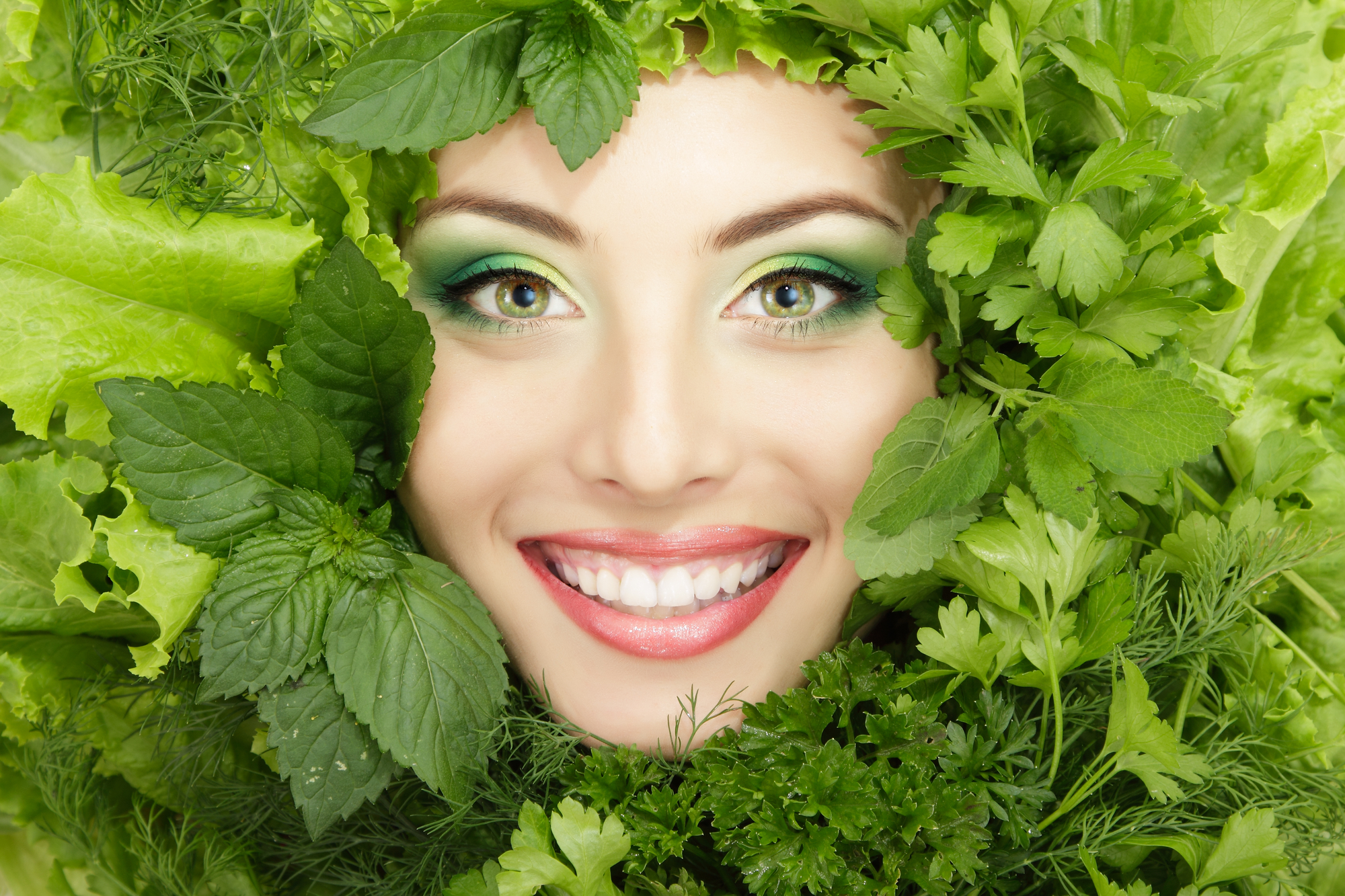 woman beauty face with greens vegetables frame isolated on white background