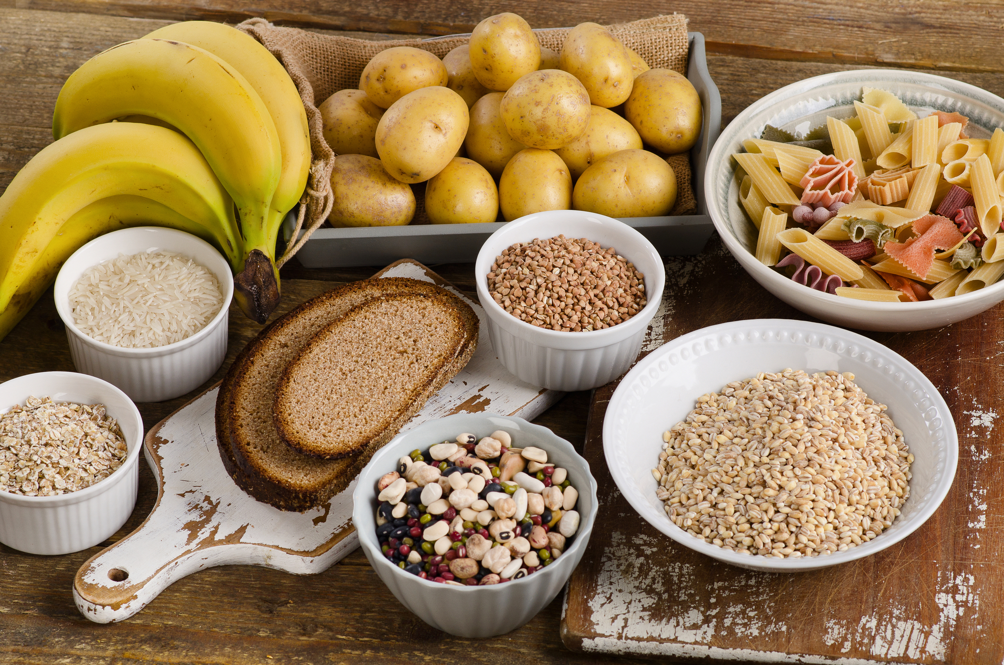 Foods high in carbohydrate on a wooden background.