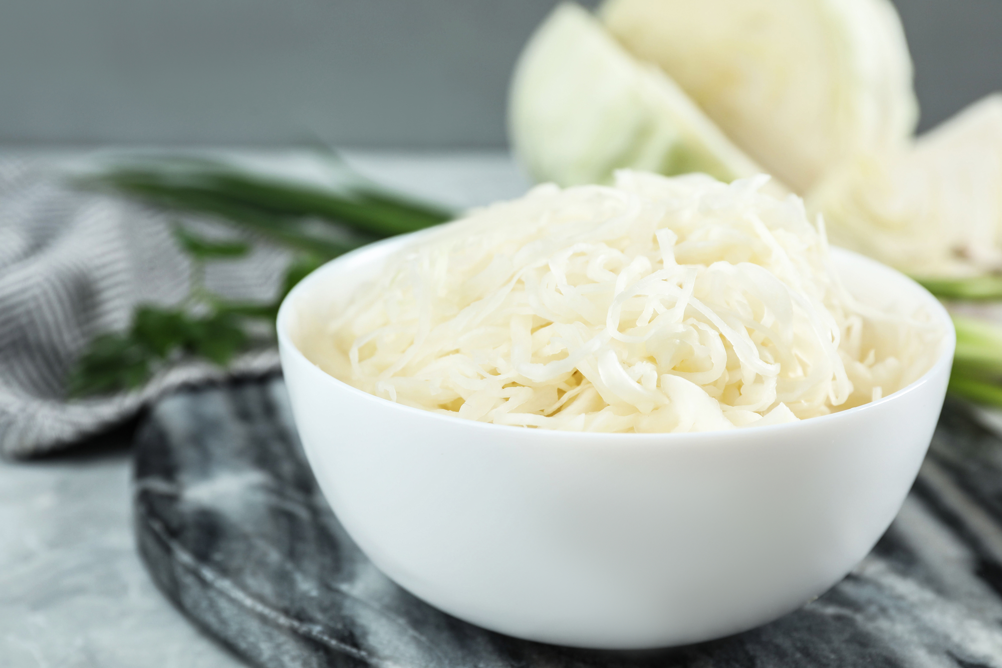 Tasty fermented cabbage on light grey table, closeup