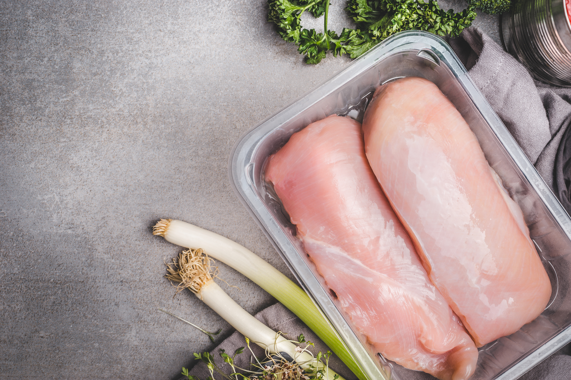 Raw chicken breast fillet in plastic box with green seasoning on concrete background
