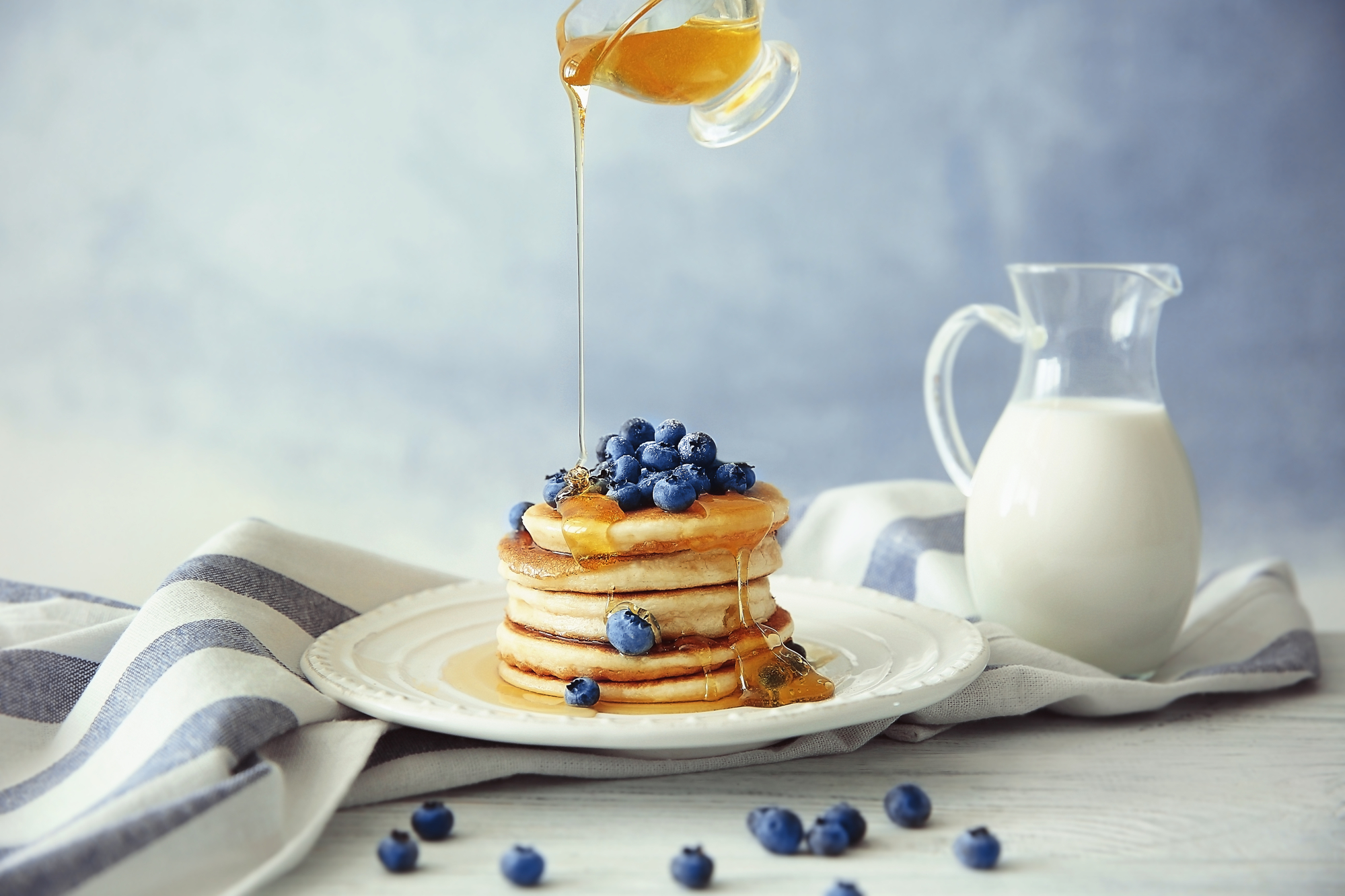 Pouring honey from gravy boat on stack of delicious pancakes with blueberries