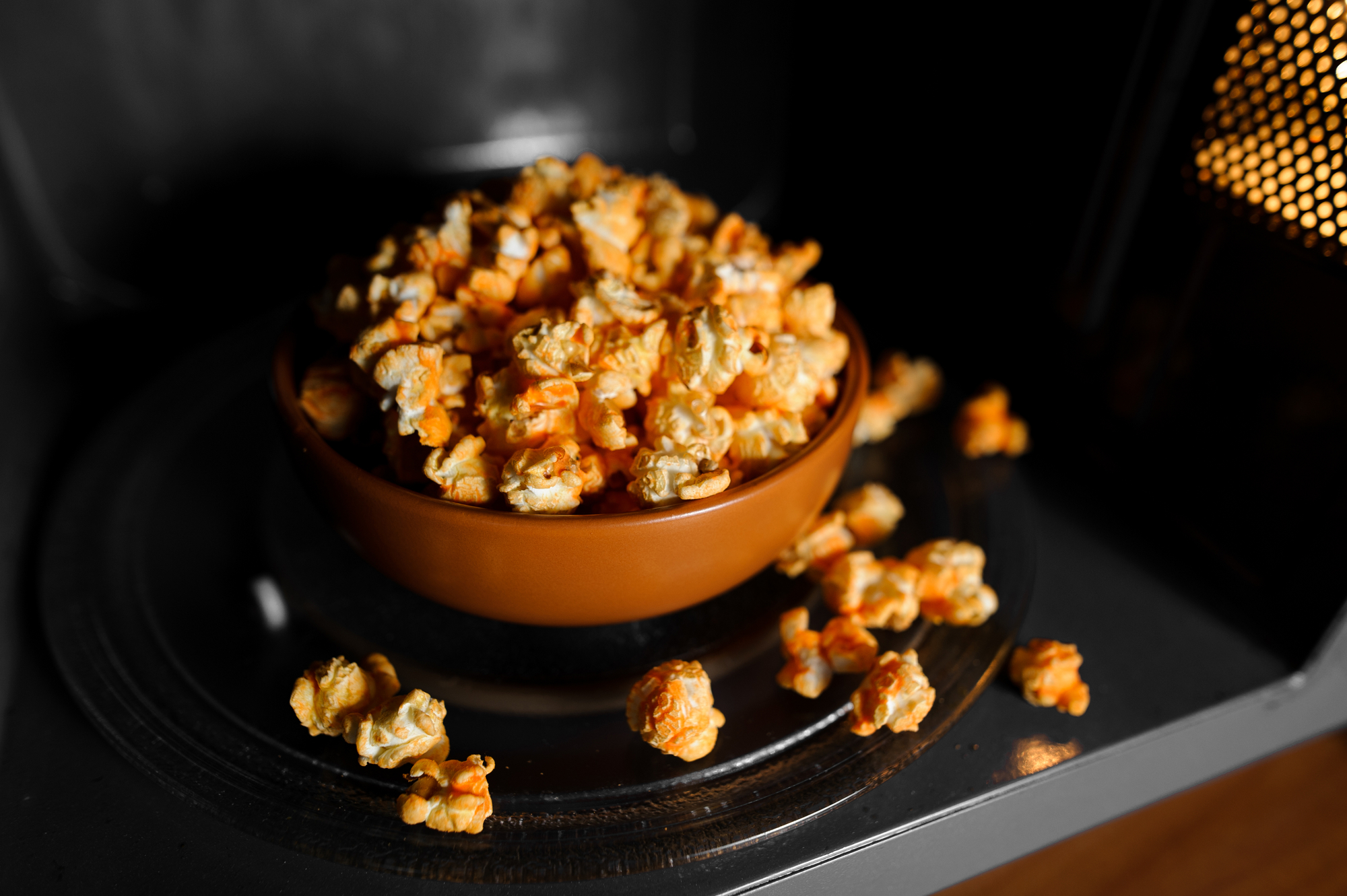 roasted popcorn in a clay brown dish stand in the microwave