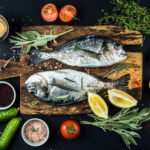 Fresh uncooked dorado or sea bream fish with lemon, herbs, oil, vegetables and spices on rustic wooden board over black backdrop