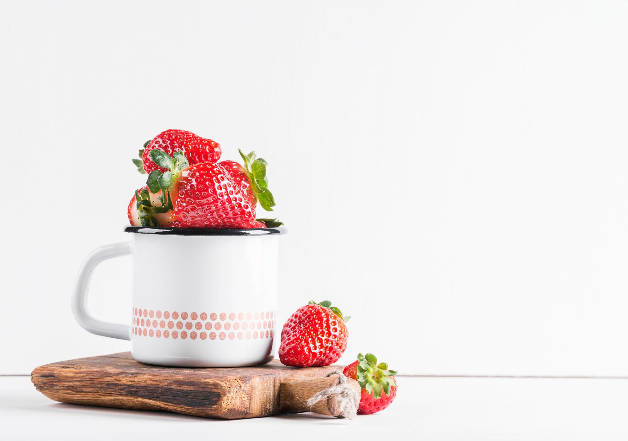 Fresh ripe red strawberries in country style enamel mug on rustic wooden board over white background