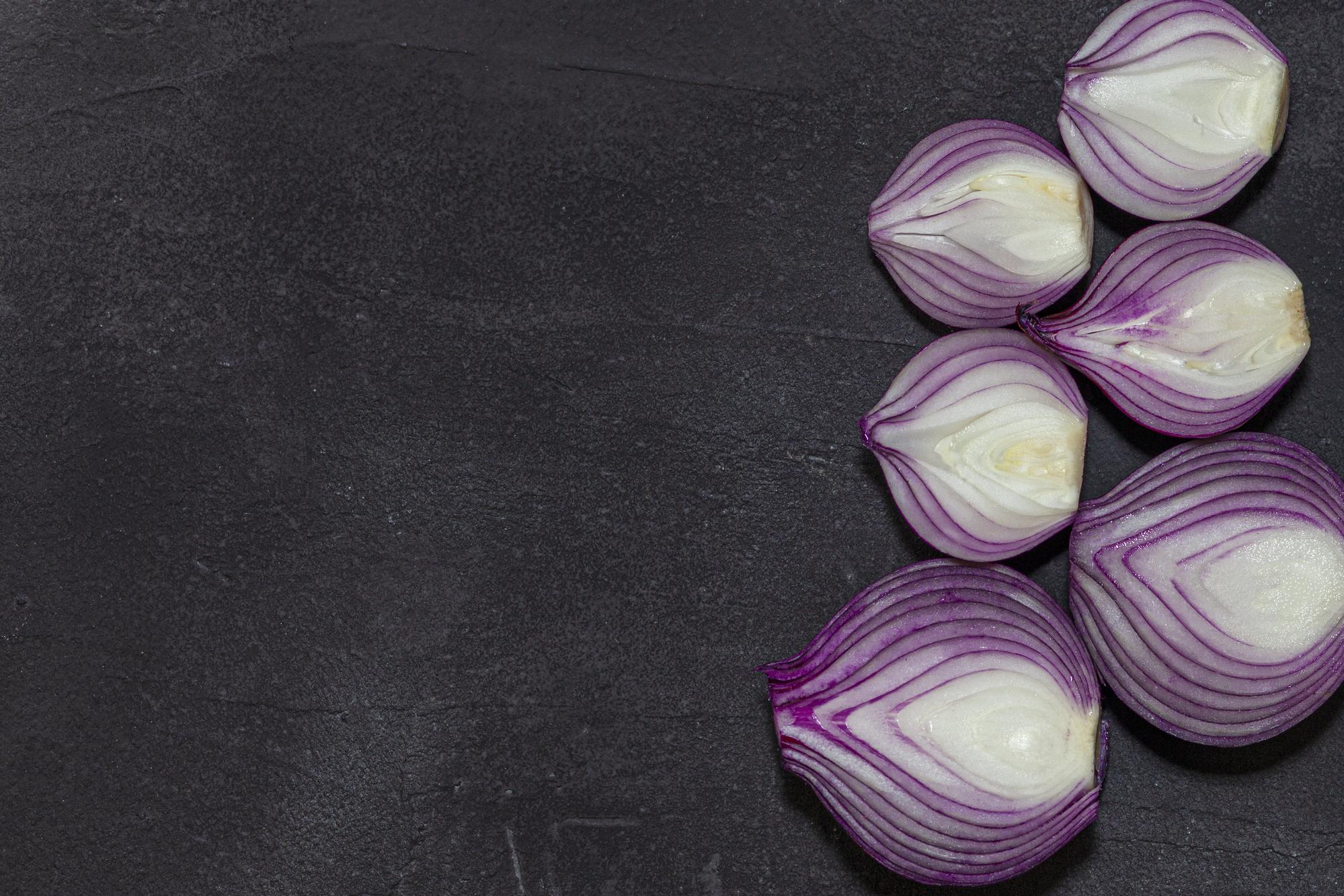 Red onion halves on a dark background